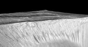 Dark narrow streaks emanate from the walls of Garni crater on Mars. A new study makes the case that they were formed by briny water flowing on the Martian surface. (NASA/JPL/University of Arizona)
