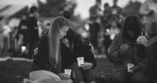 Heidi Wickersham, left, wipes away her tears while consoling her sister, Gwendolyn Wickersham, center, a UCC student who is grieving for her creative writing mentor, the slain Lawrence Levine, 67, a Umpqua Community College mass shooting victim, during candlelight vigil at a memorial service at Riverbend Park in Winston, Ore., on Saturday, Oct. 3, 2015. (Marcus Yam/Los Angeles Times/TNS)
