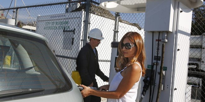 Sally Poppe, right, demonstrates filling her car at the hydrogen fuel station on Oct. 21, 2014 at Hydrogen Frontier Inc. in Burbank, Calif., owned by her husband Dan Poppe, left. Automakers are turning to another new technology - hydrogen fuel cells that have zero emissions. (Anne Cusack/Los Angeles Times/TNS)