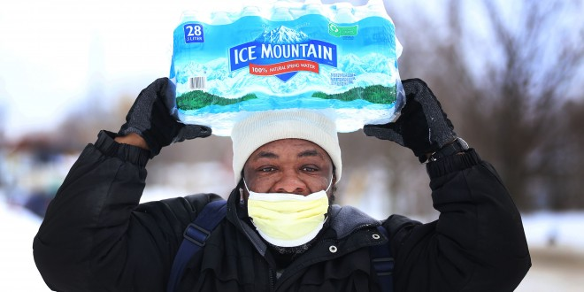 Carl Huntere, 48, of Flint, Mich., walks home through the snow from the North End Soup Kitchen in Flint on Wednesday, Jan. 13, 2016, where he received a case of free bottled water. (Regina H. Boone/Detroit Free Press/TNS)